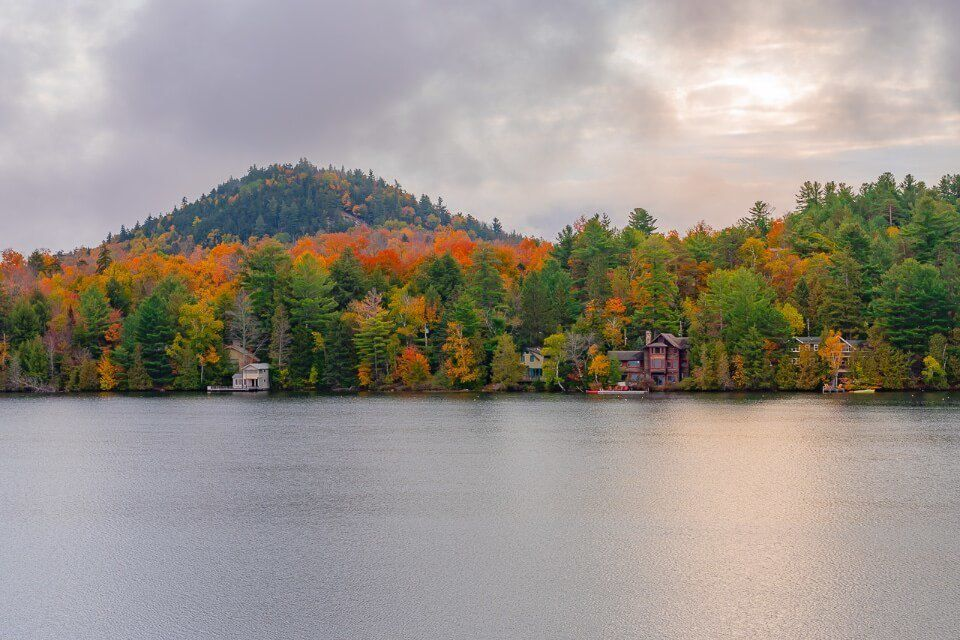 Lake Placid New York is one of the best places to stop on a fall new england road trip mirror lake stunning colors and clouds
