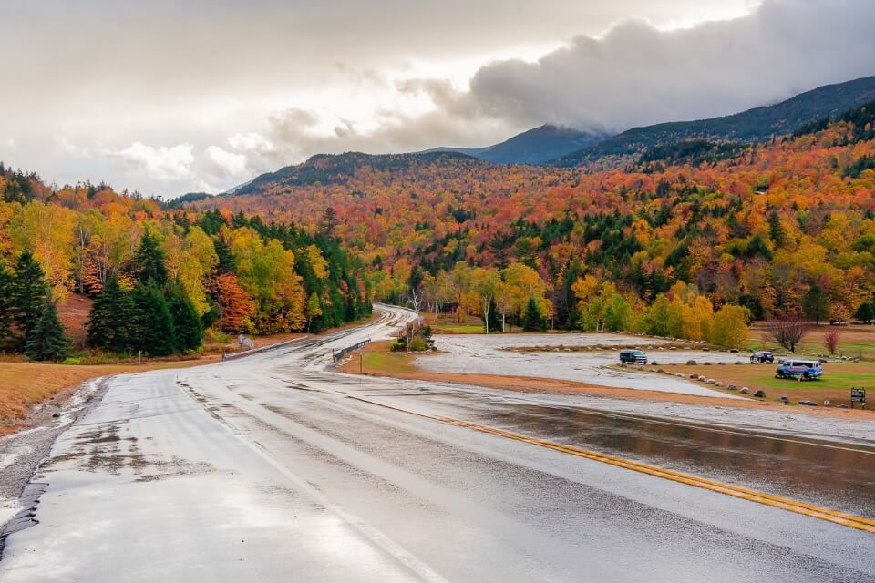 Mount Washington in New Hampshire down road and colors in trees with cloudy sky