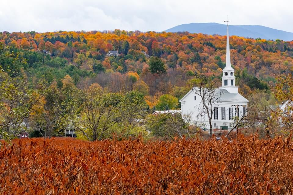 Famous Stowe white church in fall with stunning colors in hills and foreground perfect fall foliage road trip in new england stop off