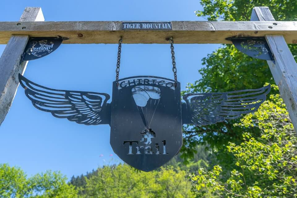 Sign with shield and wings plus parachute marking the beginning of Chirico Trail hike near seattle in washington