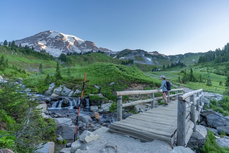 Crossing a wooden bridge overlooking Mt Rainier on skyline trail washington