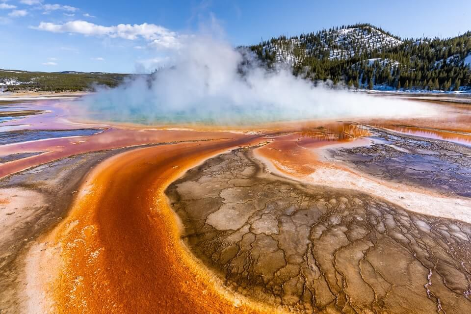 Steam billowing out of grand prismatic spring in april at yellowstone vibrant colors