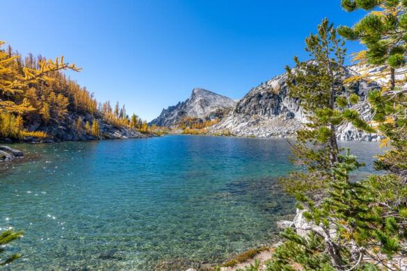 Day hiking the Enchantments trail in washington clear blue perfection lake with golden larches in peak where are those morgans hiking bucket list us trail