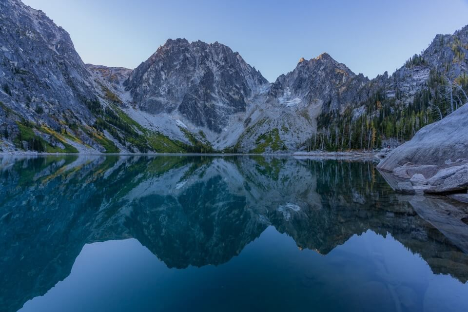 Colchuck Lake at sunrise hiking the amazing enchantments trail in washington mountain peaks reflecting in water Asgard pass to the left