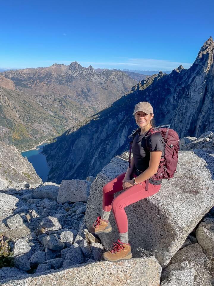 Kristen at the top of Aasgard Pass sat on a rock enjoying sunlight