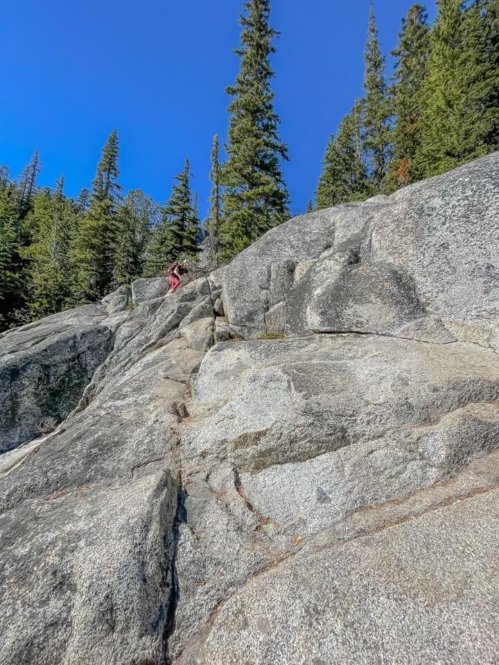 Climbing down steep granite boulder descending to snow lakes from lake viviane